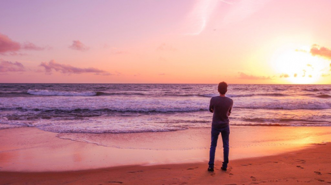 Person standing on beach looking at sunset