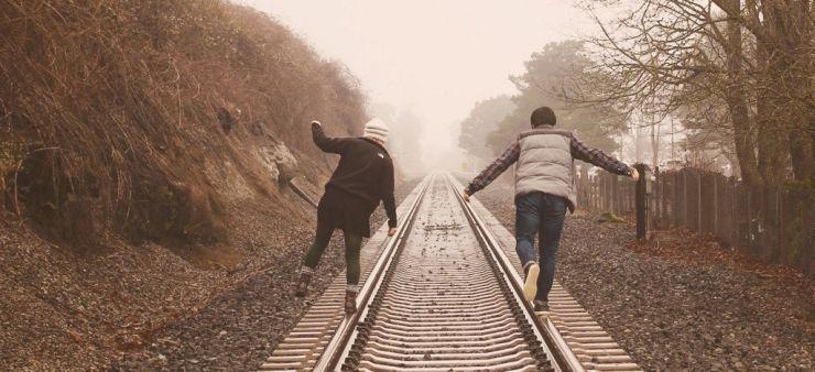 Couple balancing on train tracks