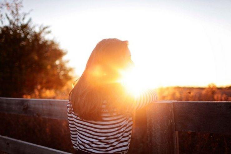 Woman next to sunset