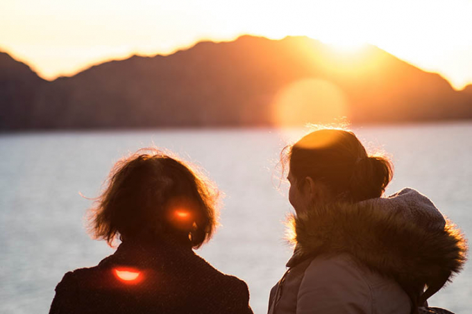 Two women looking at a lake at sunset