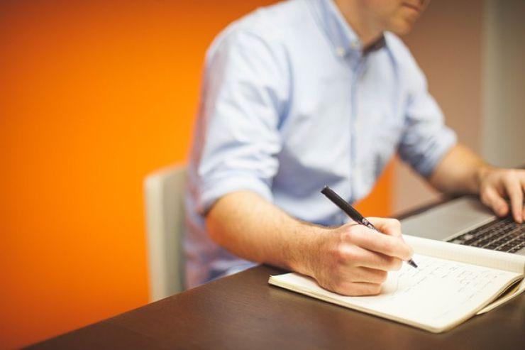 Man writing and looking at computer screen