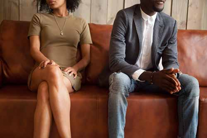 Man and woman sitting on sofa in disagreement