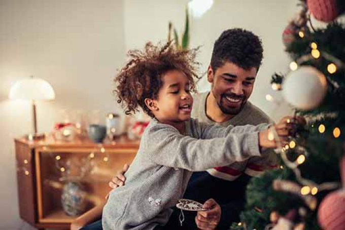 Man and child decorating christmas tree