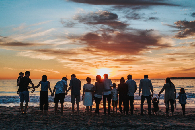 Big family on beach at sunset
