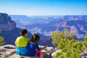 Boy and girl sitting near canyon