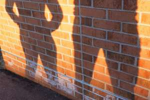 Silhouette of man and woman against brick wall