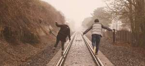 Couple balancing on train tracks