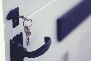 Keys in front door of house