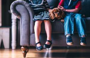 Two kids with a dog on a sofa