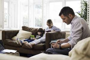 Dad on phone with two children on sofa in background