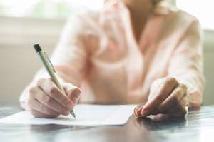 Woman signing document holding ring