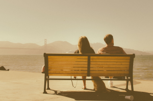 Man, woman and dog on bench looking away from each other