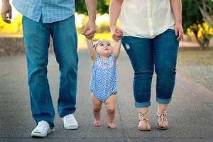 Child holding hands with parents