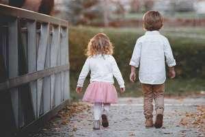 Boy and girl walking over bridge in park