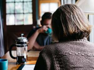 Man and woman talking whilst drinking coffee