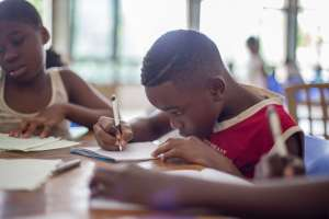 Child at school, writing on paper