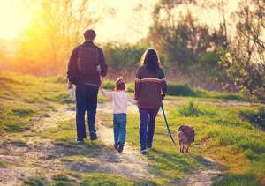 Man, little girl, woman and dog walking