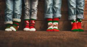 Four children wearing Christmas socks