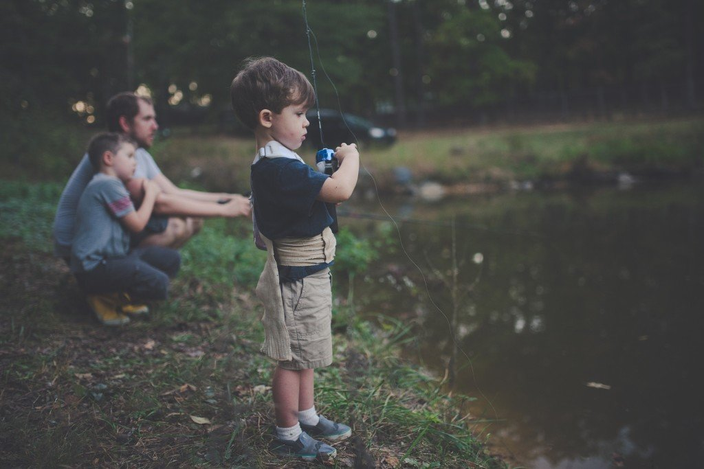 Two boys fishing with their father