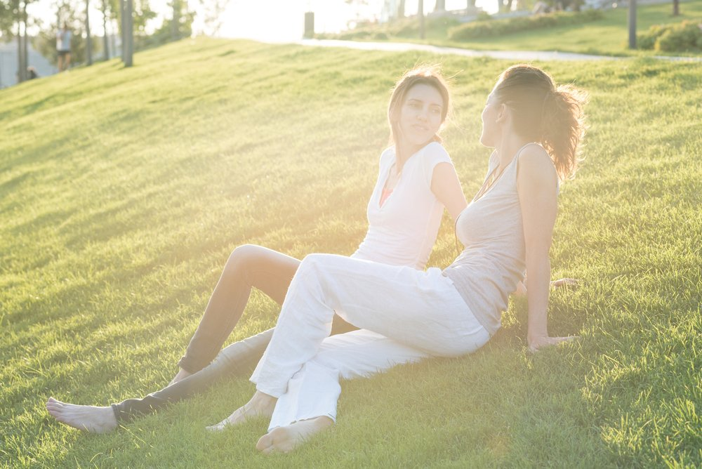 Two women lying on grass talking