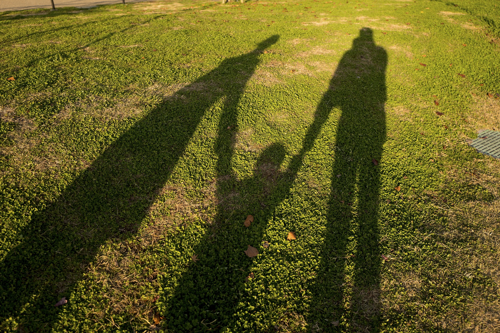 Shadow of child holding hands with parents