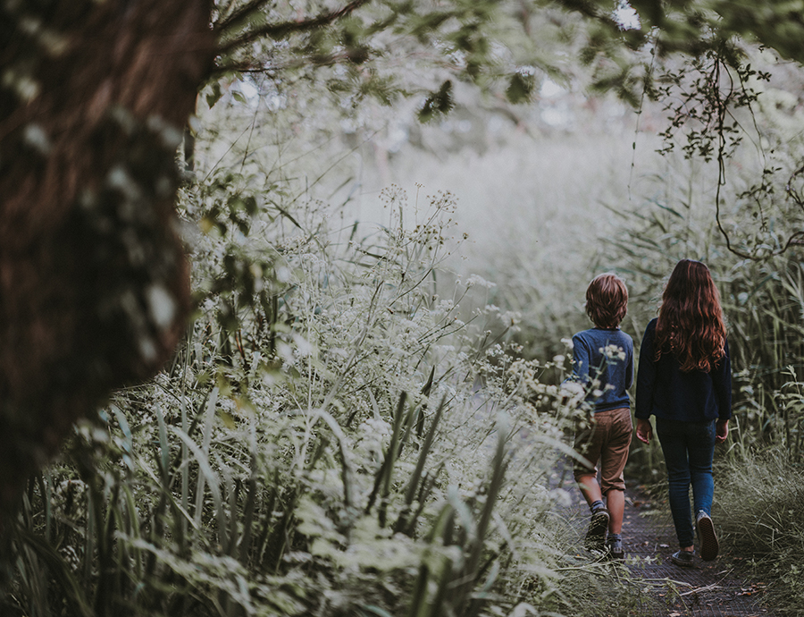 Boy and girl walking on path in long grass