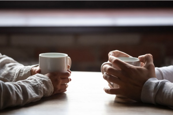 couple discussing divorce - close up of coffee mugs