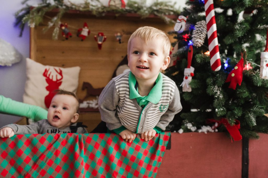 Two children in box with Christmas tree