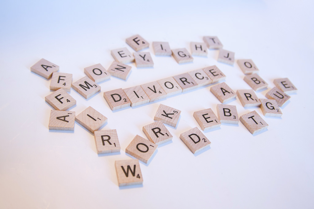 Scrabble letters arranged to spell out divorce, money fight, affair, job, argue, work and debt