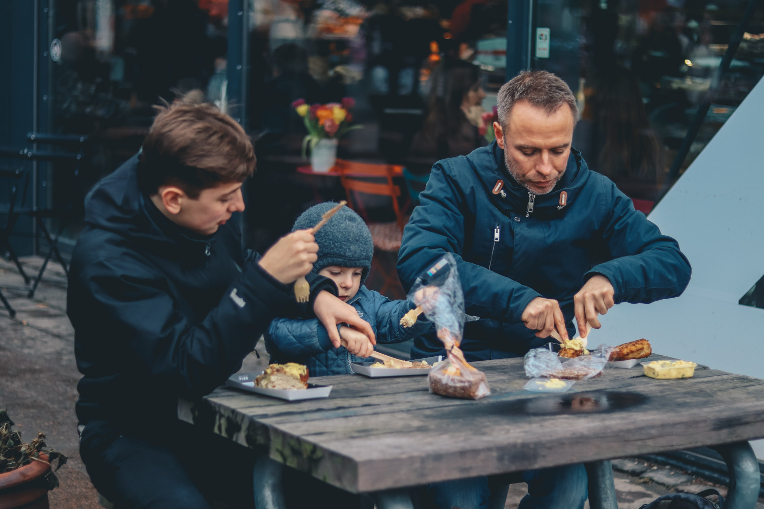 Mother, father and child eating outside