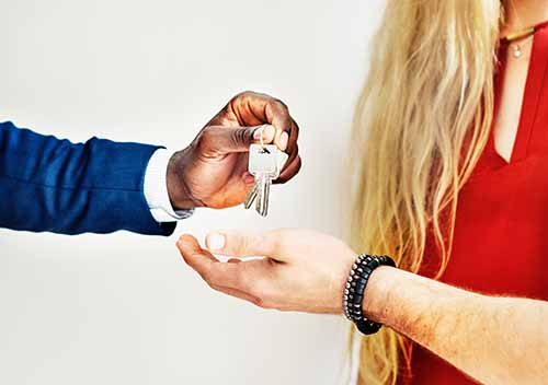 Two people handing over keys