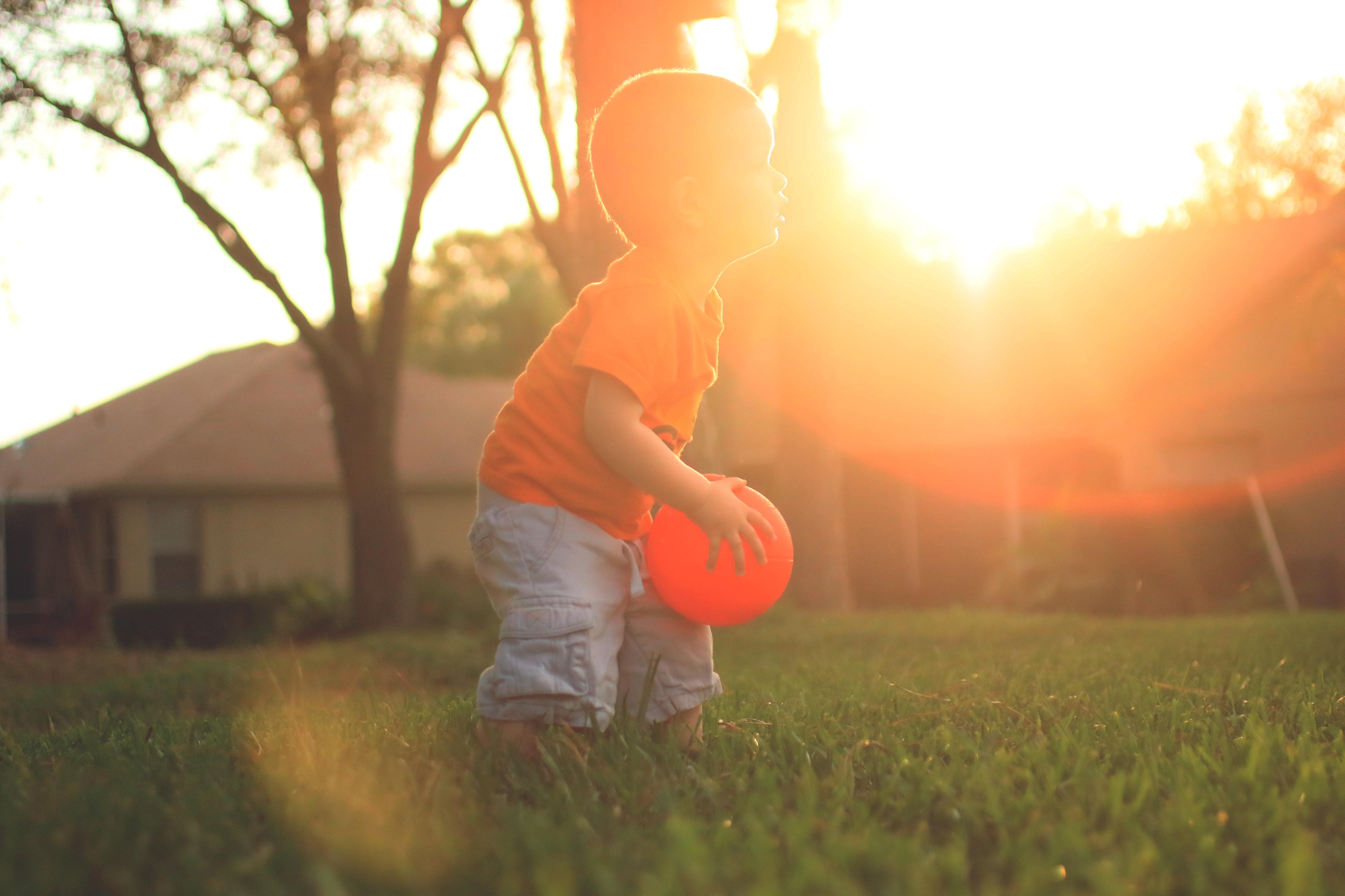 Little boy holding an orange ball